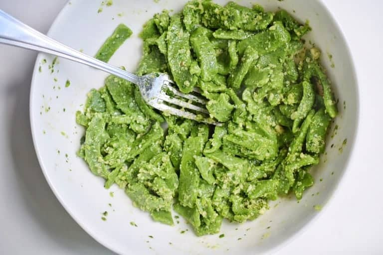 white bowl with a silver fork and green cassava flour pasta