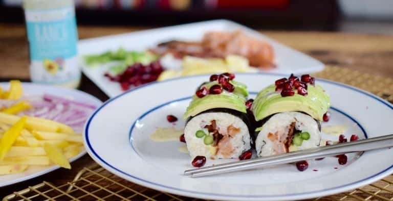sushi with avocado and pomegranate arils on a white plate