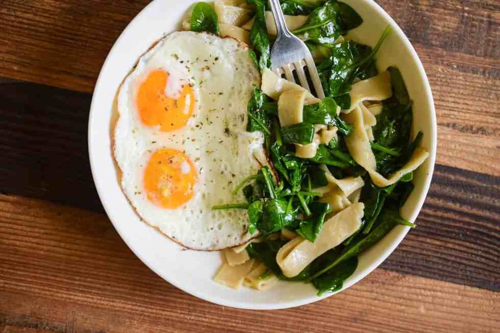 white plate with sunny side up eggs and greens and cassava flour pasta