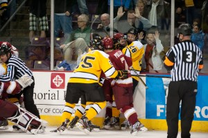 Players from Colorado College and the University of Denver in a brawl near the DU bench. Enthused fans pound on the glass in the background. Items were thrown from the fan section onto the ice, raising questions about the security at the World Arena and the violent nature of the age old rivalry. Photo courtesy of Casey B. Gibson.