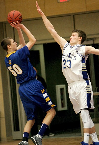 Junior guard Adam Hoffman of the Academy of Holy Angels in Richfield tries to block a shot by senior guard Bradley Carlson of Wayzata High School during the championship game of The Catholic Spirit Christmas Basketball Tournament Dec. 29 at the University of St. Thomas. Wayzata won the game, 75-70, and captured the championship for the third year in a row. This was Holy Angels' first appearance in the title game. (Dave Hrbacek / The Catholic Spirit)
