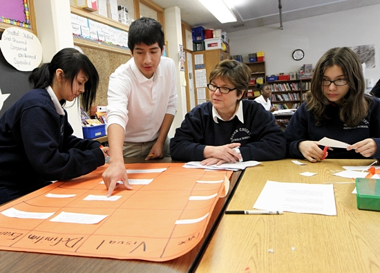Teacher Gail McCollum, second from right, helps eighth-graders Yeneira Rosario, left, Diego Romero and Argentina Lerma during reading/literature class at Risen Christ School in Minneapolis. Under a new proposal, students at the school would become bilingual in English and Spanish. Dave Hrbacek / The Catholic Spirit