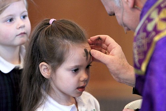 Kindergartener Josie Eisenbeis of St. Joseph School in Rosemount receives ashes from Father Paul Jarvis, pastor of St. Joseph parish, during an Ash Wednesday liturgy at the church. School students and faith formation students burned palms to create the ashes used on Ash Wednesday.