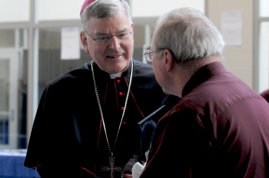 Archbishop Nienstedt talks with a participant during the breakfast break.