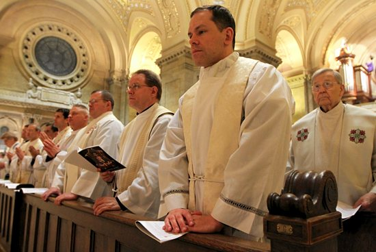Father Robert Pish of the St. Paul Seminary School of Divinity joins with other priests in the Renewal of Commitment to Priestly Service during the Chrism Mass.
