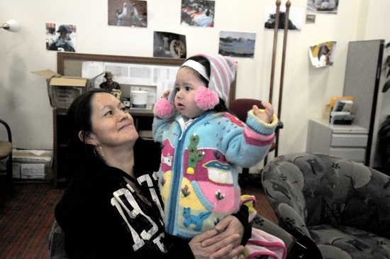 Imelda and her daughter Elena Joana, 1, sit in the Ecuadorian Consulate office in Minneapolis. The area behind them will be remodeled to house Centro Vida y Salud, a health resource center run in cooperation with St. Mary's Health Clinics. Dianne Towalski / The Catholic Spirit
