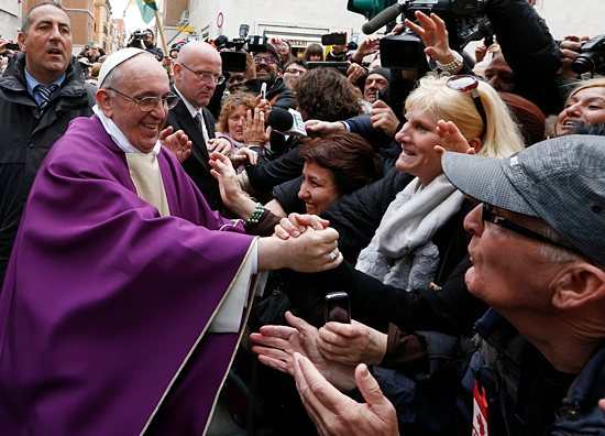 Pope Francis greets people after celebrating Mass at St. Anne Parish within the Vatican March 17. The new pope greeted every person leaving the small church and then walked over to meet people waiting around St. Anne's Gate. CNS photo / Paul Haring