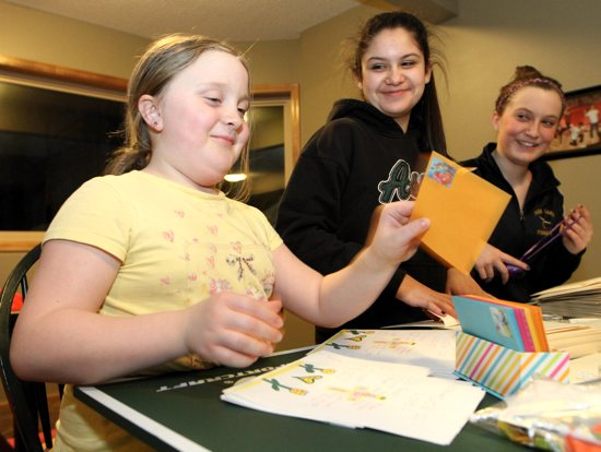 Sylvia Such, left, works to assemble care packages for her Pay it Forward project with help from her sister Sophia, right, and Sophia's friend, Kate Pakiz. Dave Hrbacek /  The Catholic Spirit