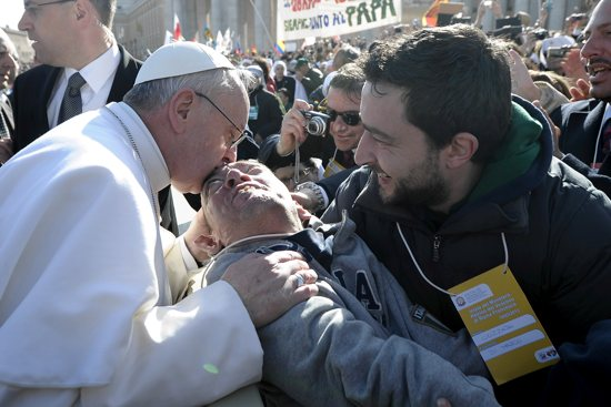 "Pope Francis kisses a disabled man after spotting him in the crowd and having his popemobile stop as he rode through St. Peter's Square March 19 ahead of his inaugural Mass at the Vatican. ""A focus of his pontificate, if we can make any assumption at this early stage, seems to be on manifest and deliberate acts of love for others,"" writes Deacon Adam Hamness. CNS photo / L'Osservatore Romano"