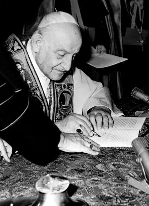 """Pope John XXIII signs his encyclical """"Pacem in Terris"""" (""""Peace on Earth"""") at the Vatican in this 1963 file photo.  CNS photo"""