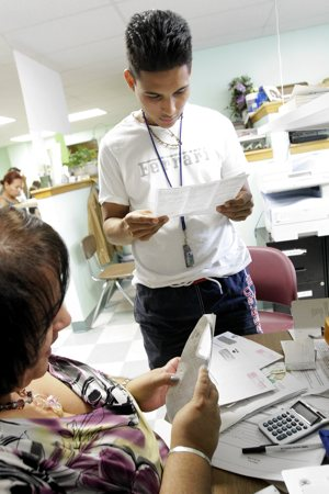 An immigrant from Honduras reviews his documents with Catholic Charities immigration counselor Margarita Rodriguez at the North Fork Spanish Apostolate offices in Riverhead, N.Y., last September. Rodriguez was on site to facilitate the application process for the Deferred Action for Childhood Arrivals program.  CNS photo /  Gregory A. Shemitz