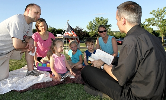 Father Michael Izen, right, pastor of St. Raphael in Crystal, reads a Bible passage during a Fortnight for Freedom prayer service at Mendakota Park in Mendota Heights June 27. Listening are, from left, John Kimec, his wife Lindsay, Lainey Kimec, Rachel Brenne, Matthias Kimec and Andi Brenne. John and Lindsay, who belong to the Cathedral of St. Paul, organized the event. The Brennes, who are their neighbors, go to a church in Minneapolis called The Rock. The Kimecs are holding a half-hour prayer service at the park every day during the Fortnight period, which runs through July 4. The services take place from 7:30 to 8 p.m., except on July 4, when it will be held at noon. Dave Hrbacek / The Catholic Spirit