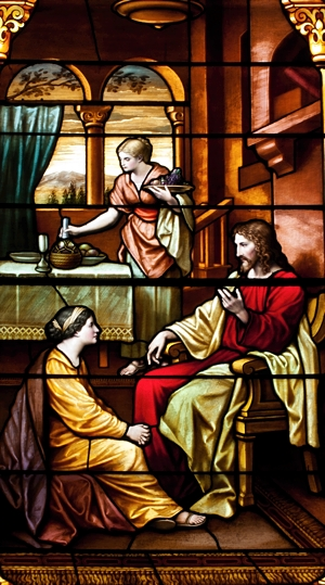 A stained glass window shows Jesus, Martha and Mary. Bigstockphoto.com
