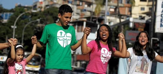 Young people carry the World Youth Day cross to city hall in Rio de Janeiro July 10 as Brazilians make final preparations for World Youth Day and the visit by Pope Francis. Young people from around the globe will join the pontiff for the celebration in Rio July 23-28. CNS photo/Pilar Olivares, Reuters