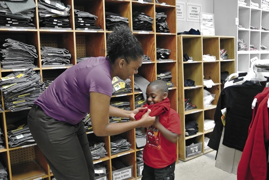 Jataun Austin helps her son Jeremiah try on a uniform sweater at Donald's Uniform in St. Paul Aug. 24. Jeremiah will be a kindergartener at Ascension School in Minneapolis. Dianne Towalski / The Catholic Spirit