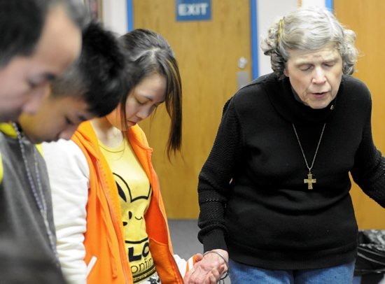 Mary Jo Copeland prays with members of a new family at Sharing and Caring Hands in Minneapolis before sending them across the street to their new temporary home at Mary's Place last February. Dianne Towalski / The Catholic Spirit