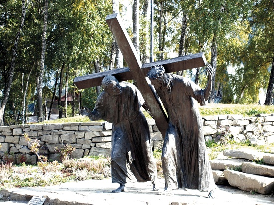 In the depiction of the fifth station, Blessed John Paul II helps Jesus carry the cross.