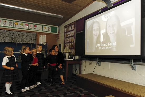 Kindergarten teacher Lauren Hallau and her students at St. Peter School in Delano watch a Spanish video produced by students at Benilde-St. Margaret's School in St. Louis Park.  Dave Hrbacek / The Catholic Spirit