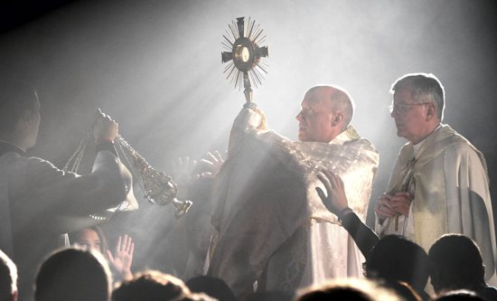 Franciscan Father David Pavonka of Steubenville, Ohio carries the Eucharist in a monstrance through the crowd, with Archbishop John Nienstedt accompanying him.