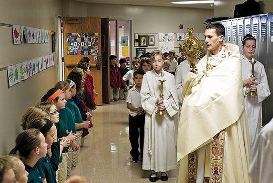 ALL SAINTS DAY: Students at All Saints Catholic School in Lakeville celebrated All Saints Day Nov. 1. Following a school Mass, students in grades K-8 knelt as an adoration procession passed by each of the classrooms. Led by Father Jonathan Kelly, assistant priest at All Saints, the second-grade students who will receive their first Communion this school year participated in the procession followed by teachers and Principal Karen Meskill.  Photo courtesy of All Saints Catholic School
