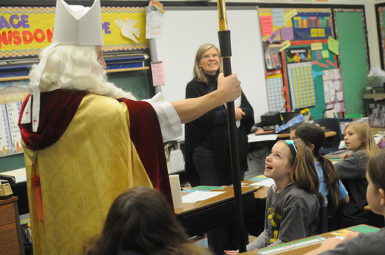 Fourth-graders Sydney Ryberg, Allison Sowatzka and Sylvia Torkelson and their teacher Mrs. Wynne listen as St. Nicholas explains how the candy can in their treat bags is like the crosier he carries.