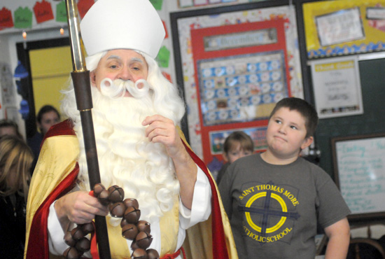 Jesuit Father Joseph Weiss, pastor of St. Thomas More parish in St. Paul, dressed as St. Nicholas Dec. 6 for a special day of activities for preschoolers and a visit to k-8 students at the parish school. Above, third-grader Declan Hegarty admires the costume.