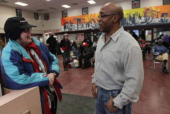 Eric Clardy, right, an advocate with Catholic Charities' Dorothy Day Center in St. Paul, talks with Sheila Jones at the center Dec. 23. Dave Hrbacek / The Catholic Spirit