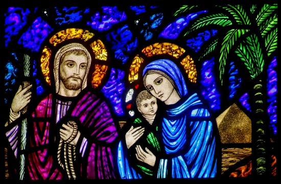 A stained-glass window shows Jesus, Mary and Joseph on their flight into Egypt.  CNS/Crosiers