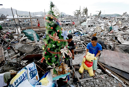 JOY AMID THE RUBBLE  A typhoon survivor decorates a Christmas tree amid the rubble of destroyed houses in Tacloban, Philippines, Dec. 17. Typhoon Haiyan reduced almost everything in its path to rubble when it swept ashore in the central Philippines Nov. 8, killing more than 6,000 people, and displacing more than 4 million. CNS photo/Erik De Castro, Reuters
