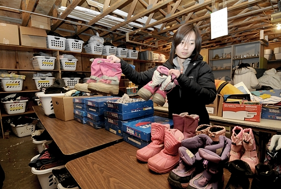 Mee Meh, a member of the Karenni Youth Conference at St. Bernard parish in St. Paul, sorts winter boots in the Free Store currently located in a garage at the parish. The conference is working with the Society of St. Vincent de Paul to open a new thrift store in the area. Dianne Towalski / The Catholic Spirit