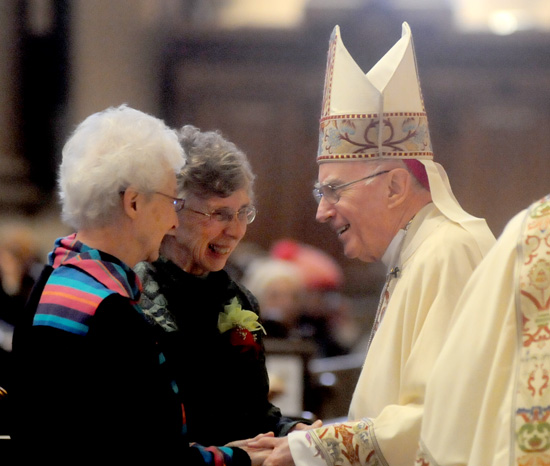 School Sister of Notre Dame Paulissa Jirik, left, and Dominican Sister Martha Wiegand laugh with Archbishop Harry Flynn during the presentation of the gifts.