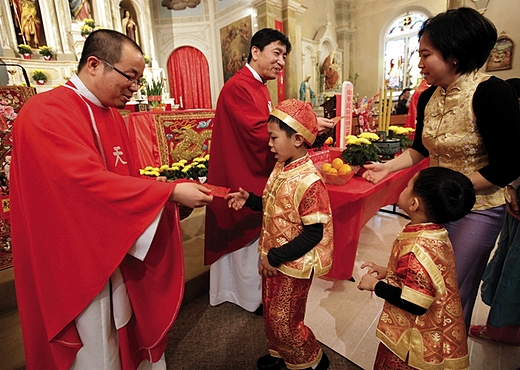CHINESE NEW YEAR: Fathers CheLong Bai and RunBao Zhang pass out red envelopes following Mass Feb. 2 at St. Therese Chinese Church in Chicago's Chinatown as part of a kick off of the Chinese lunar new year. A red envelope is a monetary or other gift given during holidays or special occasions. CNS photo/Karen Callaway/Catholic New World