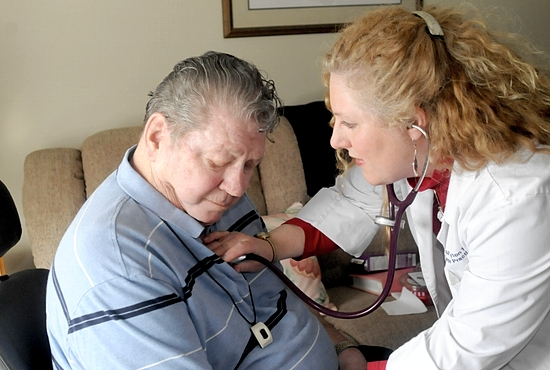 Nurse practitioner Teresa Tawil checks on Lenny Deering at the North Ridge assisted living center in New Hope Feb. 24. Tawil is a board member of Curatio: Apostolate of Catholic Health Care Professionals, which will host a bioethics conference March 28-29 in St. Paul. Dianne Towalski / The Catholic Spirit