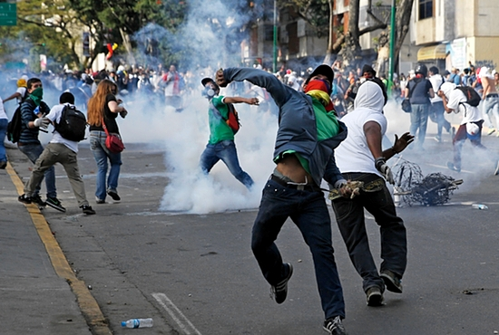 VIOLENT PROTEST: Demonstrators confront police during a protest against the government of President Nicolas Maduro in Caracas, Venezuela, Feb. 22. The country's Catholic leaders urged dialogue and respect for the demonstrators' human rights. CNS photo/Carlos Garcia Rawli ns, Reuters