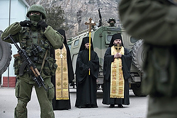 Orthodox clergymen pray near armed servicemen outside Ukrainian border guard post