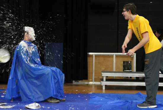 Mike Rogers, left, principal of Presentation of the Blessed Virgin Mary School in Maplewood, gets a pie in the face courtesy of seventh-grader Aaron St. Sauver on March 4 in the school gym. St. Sauver and other students got the chance to cover their  principal in whipped cream by being top sellers in the Catholic United Financial annual raffle. Rogers agreed to be the target if the school reached its goal of $24,960. A late donation of $1,000 pushed the school's total to just under $25,000, with more dollars expected to trickle in. Dave Hrbacek / The Catholic Spirit