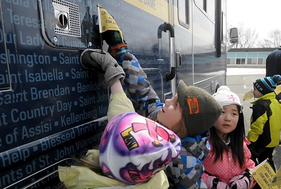Kindergarteners Dorothy Benham, Xavier Wendt and Vivian Li point out the name of their school among the names of all of the Catholic schools in the country printed on the bus during an unscheduled tour stop at Good Shepherd School in Golden Valley April 2.