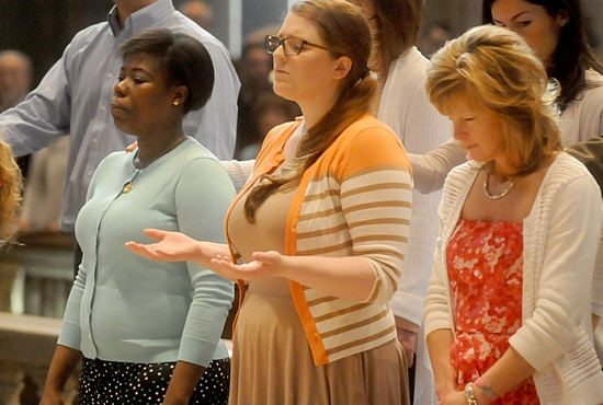 K.D. Howells (center) prays during the third scrutiny April 6 at the Basilica of St. Mary in Minneapolis, where she will become Catholic at the Easter Vigil April 19. The scrutinies serve to examine one's life and as an opportunity to pray for the grace to overcome sin. Dianne Towalski / The Catholic Spirit