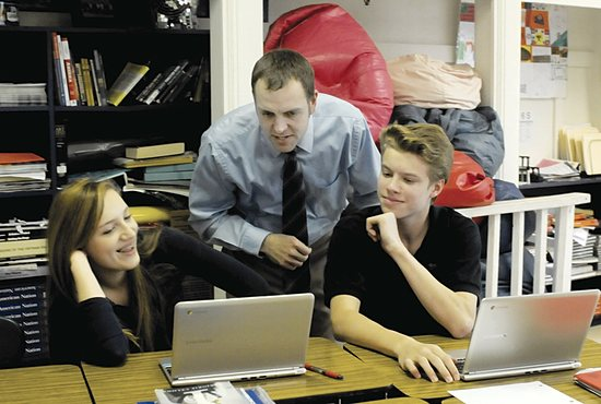 Josh Nutter, a middle school teacher at Carondelet Catholic School in Minneapolis, checks on eighth-graders Julia Hart and Jack Hower during their U.S. History class May 15. Nutter was named the K-8 Teacher of the Year by the Minnesota Independent School Forum.  Dianne Towalski/The Catholic Spirit
