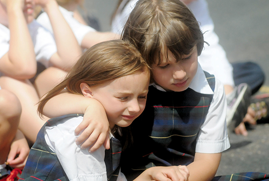 Kindergartners Mariah Tuerk, left, and Elli Petronack hug each other during the final prayer of the closing ceremony at St. Pius X School in White Bear Lake June 5. Dianne Towalski / The Catholic Spirit