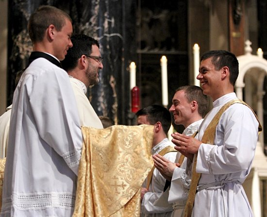 From left, Dominic Shovelain and Father Peter Richards, pastor of St. Michael in St. Michael, help newly ordained Father Paul Shovelain put on his stole and chasuble during investiture at the ordination Mass. Father Shovelain grew up attending St. Michael.