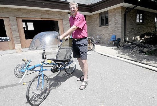 Deacon Mick Humbert visits Hope for the Journey Home shelter at Guardian Angels in Oakdale June 10. Proceeds from his fundraising bike ride from Alaska to the Twin Cities will help pay for a renovation project to turn the shelter's garage into a large family room. Dianne Towalski / The Catholic Spirit
