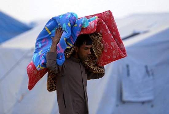 REFUGEE CAMP An Iraqi refugee carries a mattress at a camp near the northern city of Irbil June 12. Hundreds of thousands of people who have fled their homes in Mosul are left without access to aid, officials said. Christians from the city say they were targeted long before Iraqi security forces abandoned the major political and economic hub. CNS photo/Stringer, EPA