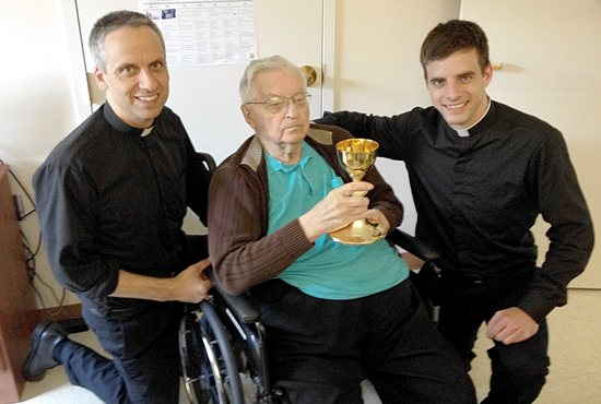 "PASSING THE CHALICE Msgr. Stanley Srnec, center, poses for a photo with Father Michael Izen, left, pastor of St. Raphael in Crystal, and newly-ordained Father Marcus Milless, parochial vicar of All Saints in Lakeville, at the Leo C. Byrne Residence in St. Paul July 3. The chalice he holds, which features an inscription from his parents and his mother's wedding diamond, was given to him for his ordination in 1942. It was handed down to Father Milless, but the two had never met. After reading a story in The Catholic Spirit (""New priests share the stories of their chalices;"" June 5, 2014, pages 10 and 11) Father Izen introduced the two. Photo courtesy of Father Michael Izen"