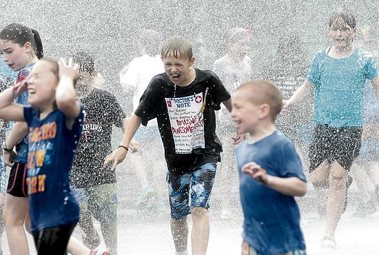 Matthew Narog, center, runs through the spray as a truck from the St. Anthony Village Fire Department sends a stream of water over the parking lot at  St. Charles Borromeo in St. Anthony July 11.
