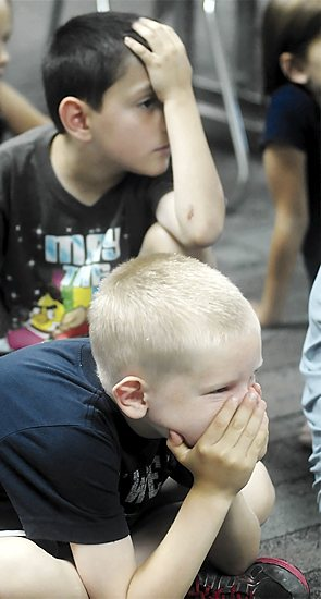 """Boys in the first- and second-grade class show frustration as they compete in a game of hangman to learn the word, """"transubstantiation."""""""