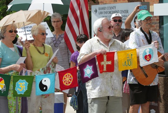 Participants at the vigil hold up interfaith prayer flags to express that the issue concerns all world religions.
