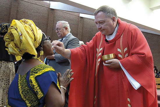 A parishioner of St. Alphonsus in Brooklyn Center receives the Eucharist from Redemptorist Father Steven Nyl. St. Alphonsus has a large African population, some of whom have lost family members and friends to the deadly Ebola virus. Jim Bovin/For The Catholic Spirit