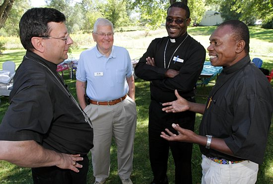 From left, Bishop Lee Piché, Deacon George Nugent, Bishop Gabriel Malzaire and Father Godfrey Tarimo visit at a picnic Sept. 7 at the home of Charlene and Duane Breid of All Saints in Lakeville. Bishop Malzaire and Father Tarimo came to Minnesota to say thanks to parishioners at All Saints for the money they donated to help rebuild St. Andrew Church in Dominica after it was leveled by an earthquake in 2004. Dave Hrbacek/The Catholic Spirit