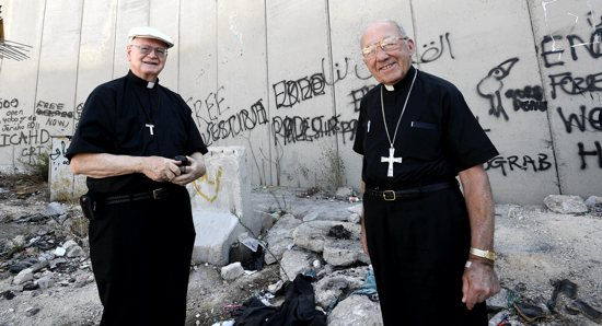 BISHOPS VISIT HOLY LAND Retired Bishop Bernard Harrington of Winona and retired Archbishop Eusebius Beltran of Oklahoma City stand in front of the Israeli separation wall near Jerusalem Sept. 12. Eighteen bishops went on a nine-day prayer pilgrimage for peace in the Holy Land. A member of the delegation said they left with a stronger resolve to advocate for peace and to urge the U.S. government to take a leadership role in ushering Israelis and Palestinians toward peace. CNS/Debbie Hill